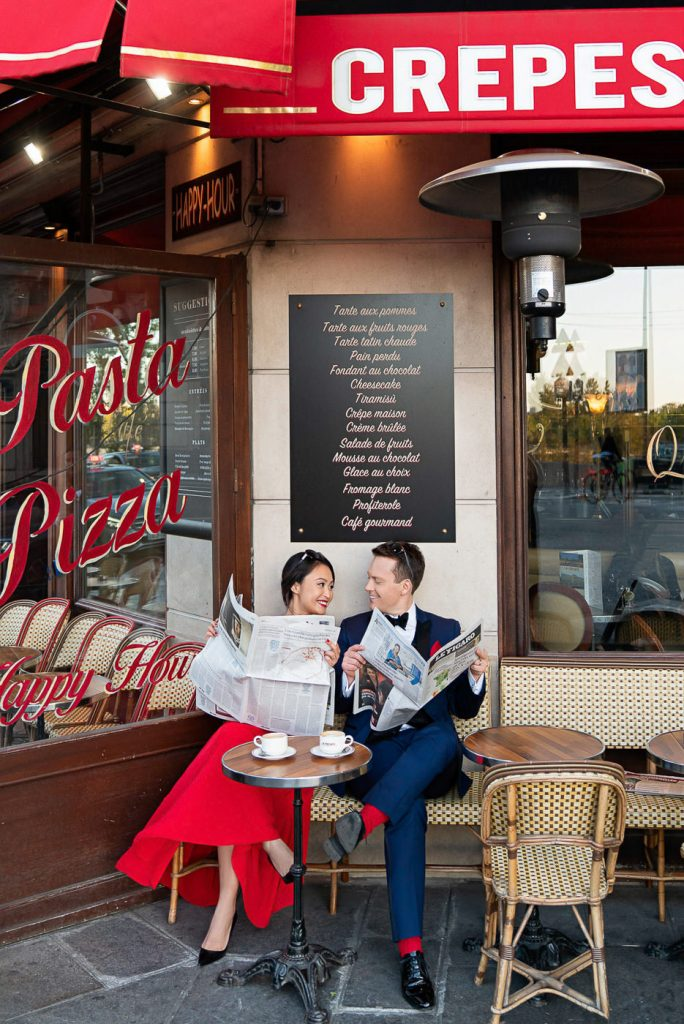 Couple reading newspapers at a Cafe for their Paris engagement photos
