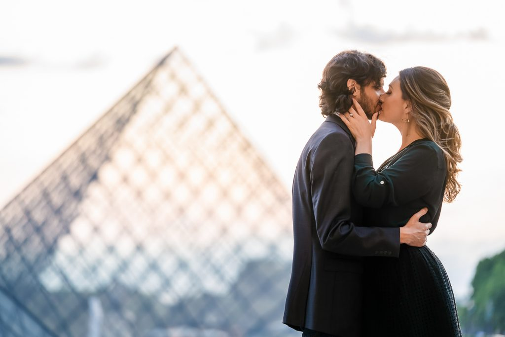 Couple kissing at the Louvre Pyramid at sunset