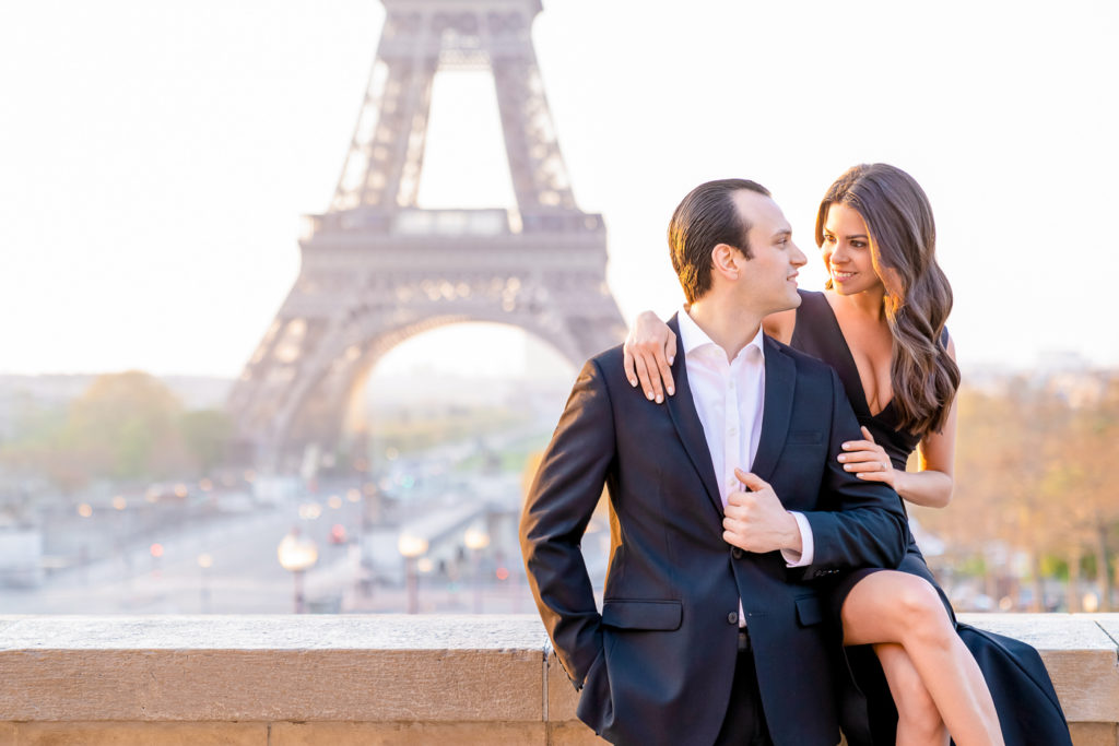 Beautiful couple engagement pose of a couple sitting on a wall at Trocadero during sunrise