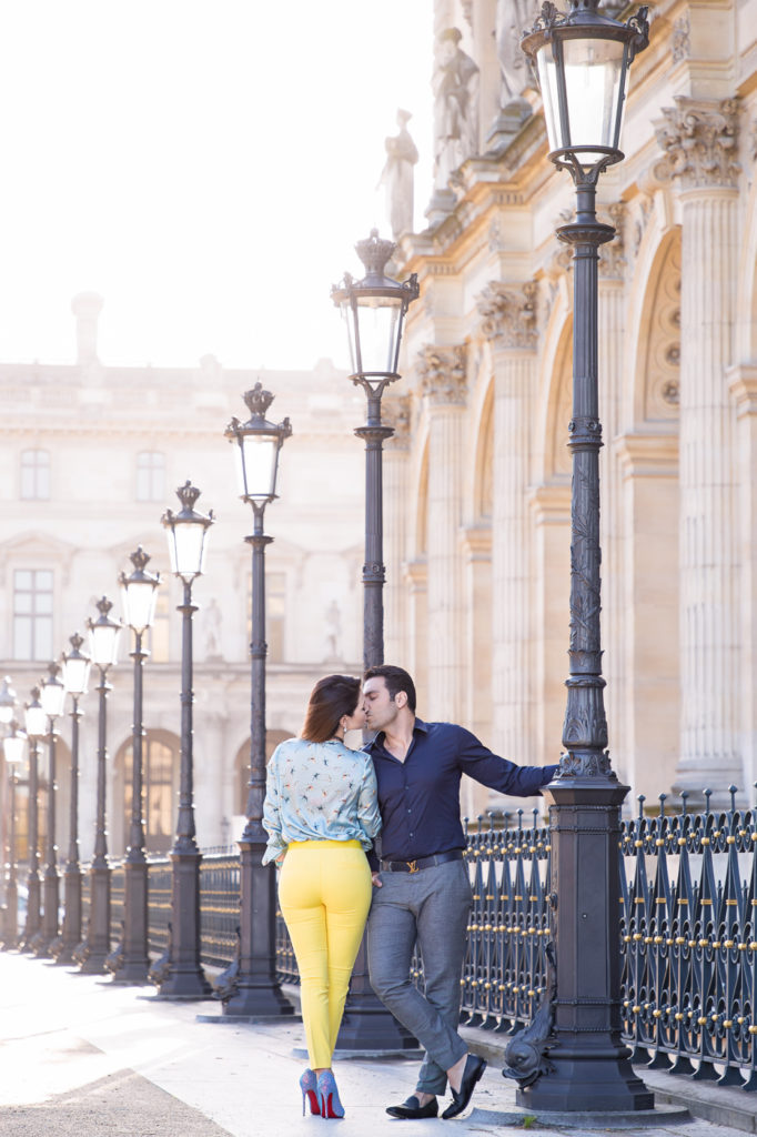 Stylish couple kissing during their Paris engagement shoot near the Louvre Museum at sunrise