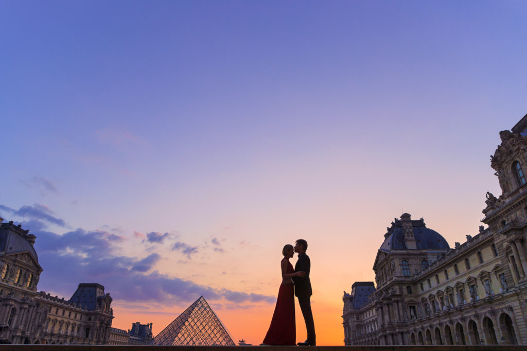 Stunning nighttime Paris engagement photo at the Louvre taken during the romantic Blue Hour
