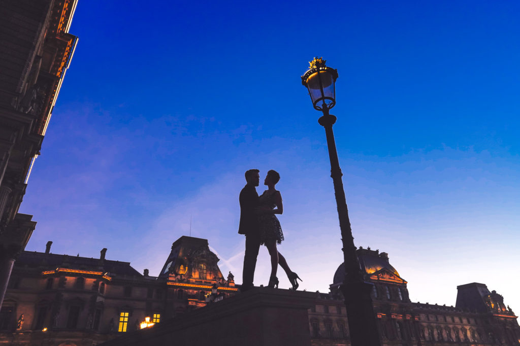 Silhouette couple engagement photos at the Louvre during the Blue Hour