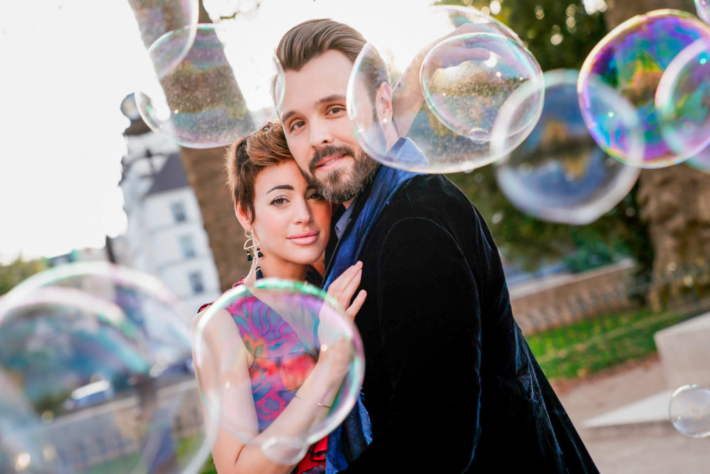 Creative Paris engagement photo with massive bubbles used as a prop