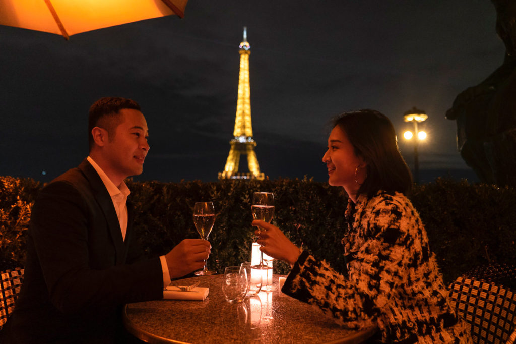 Nighttime Eiffel Tower engagement photos at Cafe de l'Homme with Champagne
