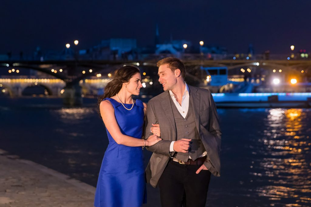 Romantic photo with couple strolling along the Seine at night