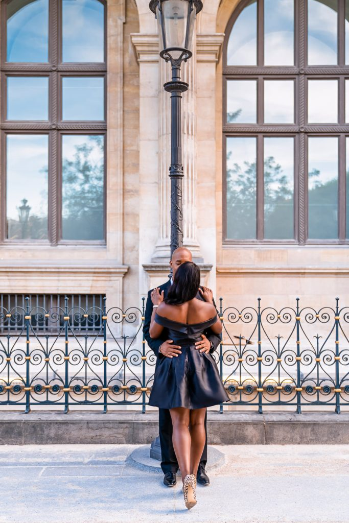 Couple stealing naughty kisses at the Louvre in the evening