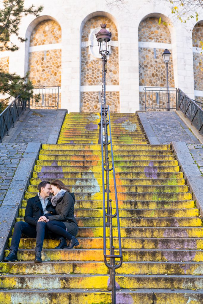 Couple doing engagement photos on colorful stairs at Montmartre