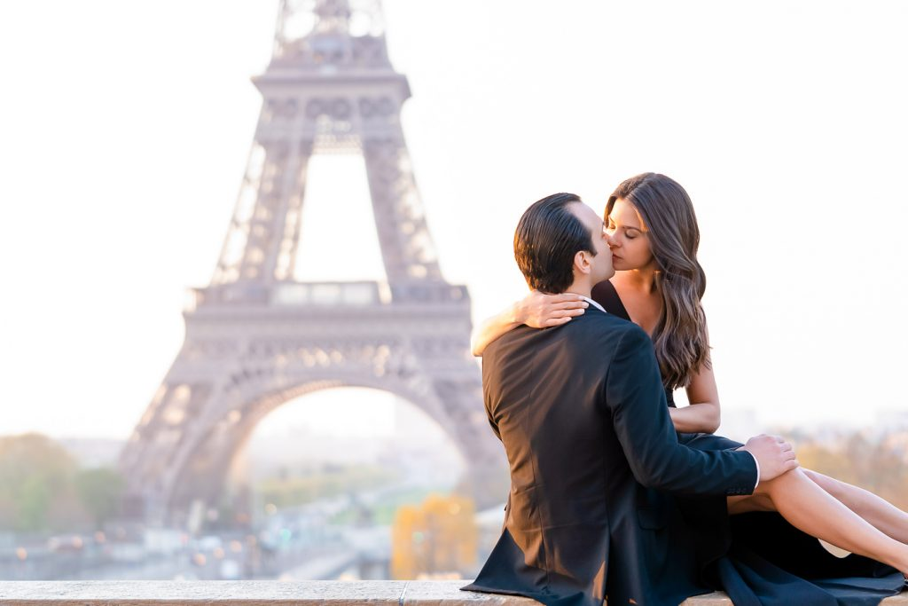 Amazing engagement photo ideas with the couple sitting on the wall at Trocadero Eiffel Tower view